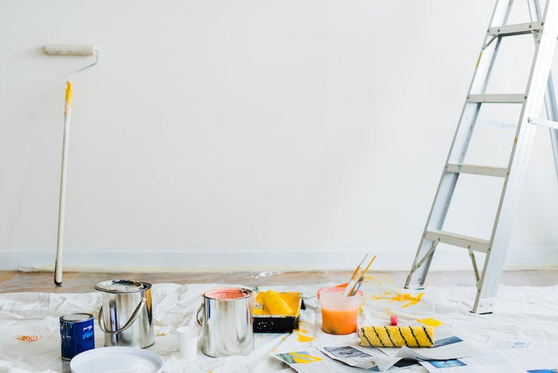 Ladder and painting supplies in white room