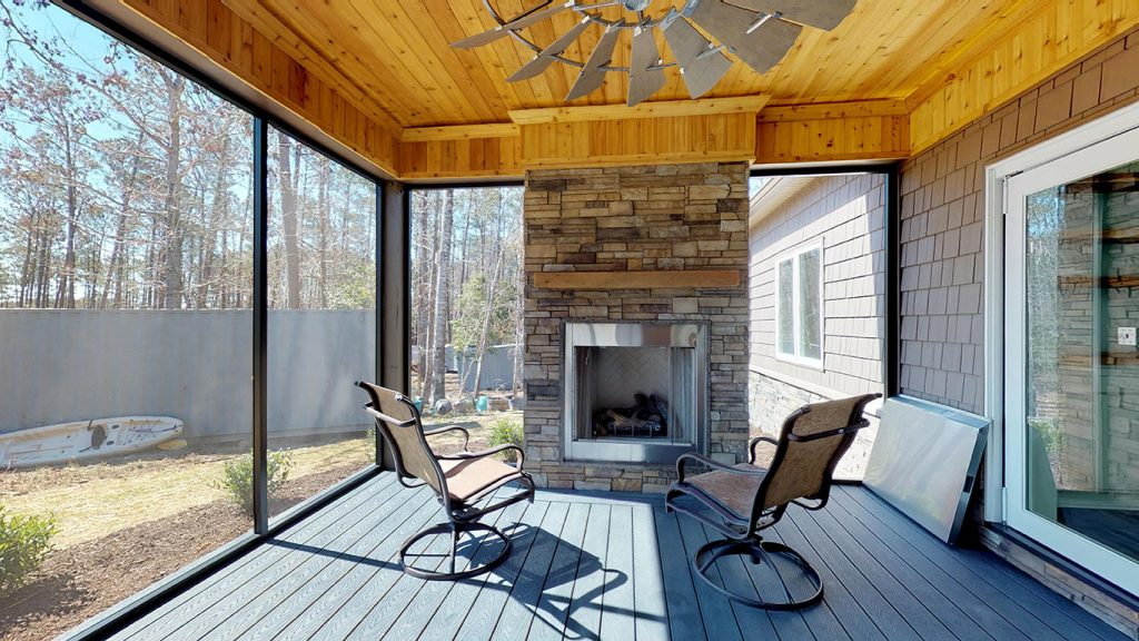 Back porch with fireplace built into a custom home by C.O.D. Home Services, Emerald Isle, NC.
