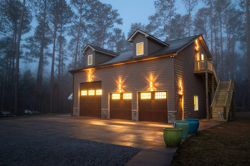 Light glowing from freestanding garage with in-law suite above by C.O.D. Home Services.
