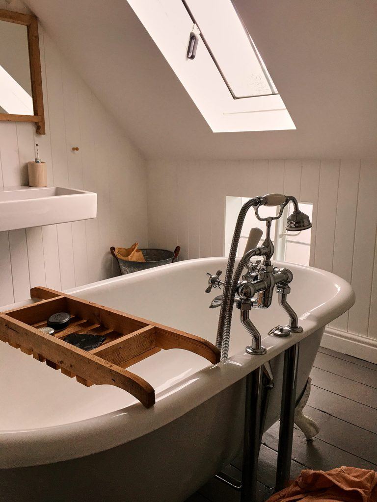 Small, sloped-roof bathroom with a skylight and extra window.