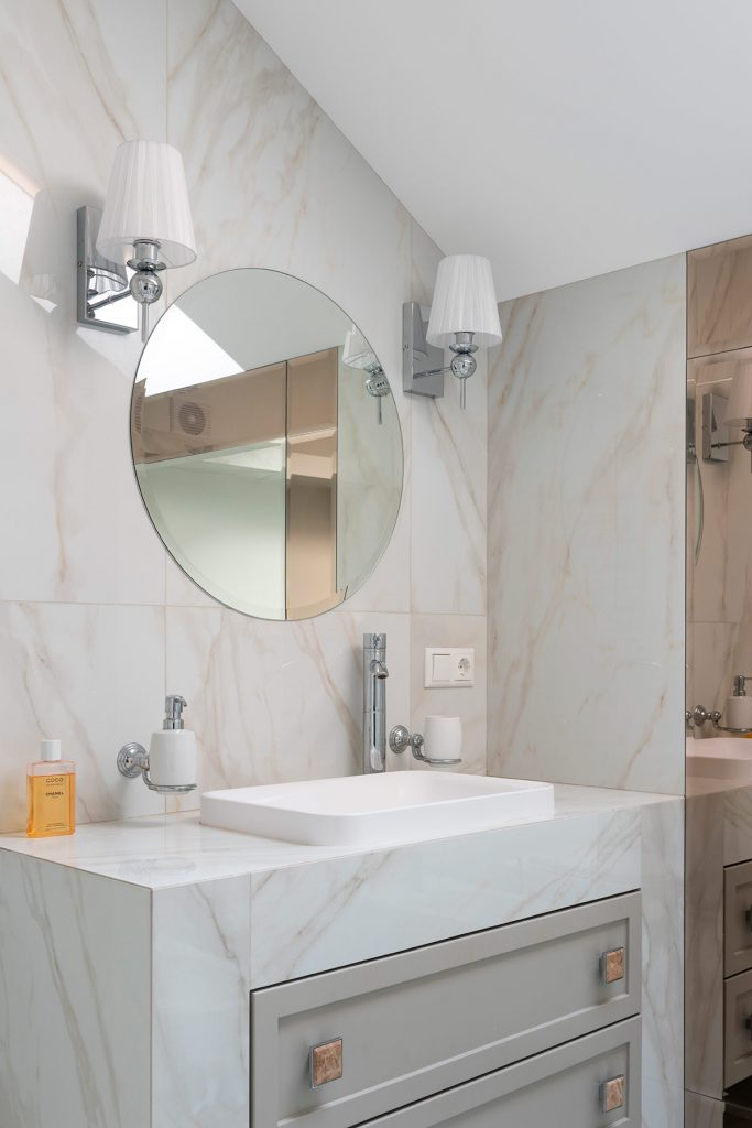 Bathroom with small vanity and larger mirror to feel larger.