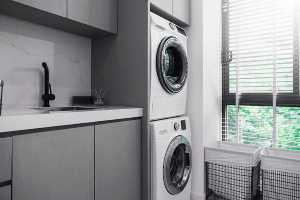 A bright and orderly laundry room with stackable washer and dryer