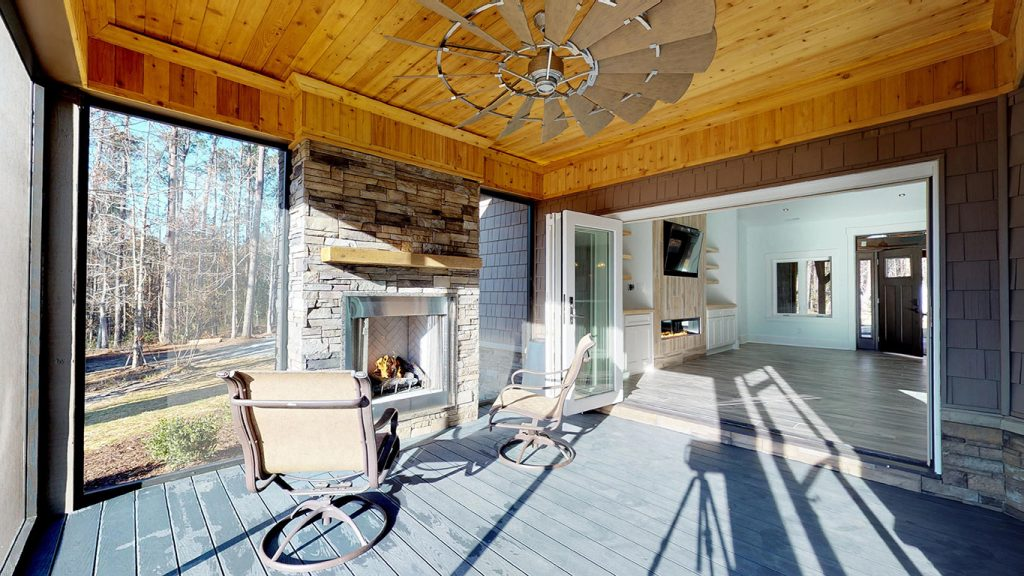 Covered porch with ceiling fan and a fireplace provides plenty of outdoor space for renters.